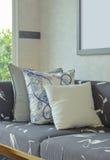 Διακοσμητικά μαξιλάρια που θέτουν στον καναπέ με την ξύλινη βάση στο livi Στοκ Εικόνες