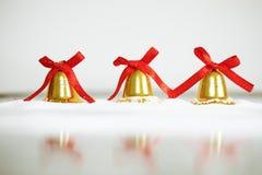 Διακοσμητικά χρυσά κουδούνια για τα Χριστούγεννα και το νέο έτος, στο άσπρο χιόνι, με το διάστημα αντιγράφων Στοκ Εικόνες