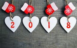 Διακοσμητικές άσπρες ξύλινες καρδιές Χριστουγέννων και κόκκινα γάντια με 2018 αριθμούς στο ξύλινο υπόβαθρο με το διάστημα αντιγρά Στοκ Εικόνες