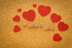 Διακοσμητικές καρδιές και εγγραφή, σ' αγαπώ, στο λαμπρό χρυσό υπόβαθρο ως σύμβολο της αγάπης μαζί με μια θέση για το δ σας Στοκ Εικόνες