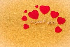 Διακοσμητικές καρδιές και εγγραφή, σ' αγαπώ, στο λαμπρό χρυσό υπόβαθρο ως σύμβολο της αγάπης μαζί με μια θέση για το δ σας Στοκ Φωτογραφίες