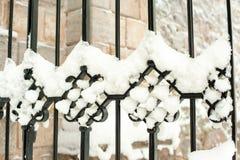 Διακοσμητικές μαύρες καμπύλες φρακτών μετάλλων που καλύπτονται με το χιόνι Στοκ Εικόνα