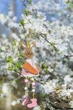 Διακοσμητική ένωση λαγουδάκι Πάσχας στους κλάδους ενός ανθίζοντας δέντρου κερασιών Στοκ Εικόνα