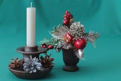 Διακοσμητική ανθοδέσμη Χριστουγέννων σε ένα κεραμικό βάζο και ένα κεραμικό κηροπήγιο με ένα άσπρο κερί κεριών και πολύχρωμοι κώνο στοκ εικόνες με δικαίωμα ελεύθερης χρήσης