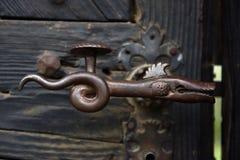 Διακοσμητική εκλεκτής ποιότητας λαβή πορτών σιδήρου στην ξύλινη πόρτα Στοκ φωτογραφίες με δικαίωμα ελεύθερης χρήσης