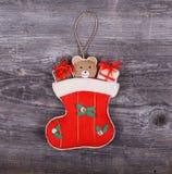 Διακοσμητική διακόσμηση Χριστουγέννων - δώρα στα άλογα καλτσών στο ξύλινο β Στοκ εικόνα με δικαίωμα ελεύθερης χρήσης