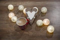 Διακοσμητική καρδιά, φω'τα και φλιτζάνι του καφέ στον ξύλινο πίνακα Στοκ εικόνες με δικαίωμα ελεύθερης χρήσης