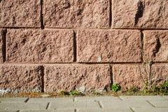 Διακοσμητική μίμηση της ρόδινης πλινθοδομής - ο τοίχος του σπιτιού και του πεζοδρομίου r στοκ φωτογραφίες