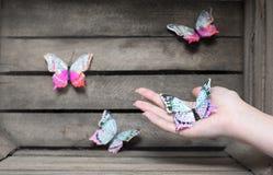 Διακοσμητική πεταλούδα σε ένα ξύλινο υπόβαθρο χεριών στοκ εικόνες με δικαίωμα ελεύθερης χρήσης