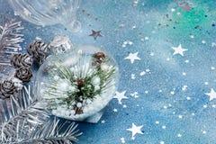 Διακοσμητική σφαίρα γυαλιού με τον κλάδο χριστουγεννιάτικων δέντρων στο μπλε sparkli Στοκ φωτογραφία με δικαίωμα ελεύθερης χρήσης