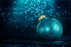 Διακοσμητική σφαίρα χριστουγεννιάτικων δέντρων μπροστά από το λαμπιρίζοντας υπόβαθρο Στοκ Εικόνα