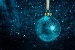 Διακοσμητική σφαίρα χριστουγεννιάτικων δέντρων μπροστά από το λαμπιρίζοντας υπόβαθρο Στοκ Φωτογραφία