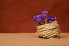 Διακοσμητική σύνθεση του σπάγγου και των λουλουδιών σε ένα καφετί υπόβαθρο Στοκ Εικόνες