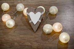 Διακοσμητική χειροποίητη καρδιά και φω'τα στον ξύλινο πίνακα Στοκ Εικόνες