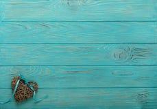 Διακοσμητική ψάθινη καρδιά του γκρίζου χρώματος με μια μπλε κορδέλλα σε ένα wo Στοκ εικόνα με δικαίωμα ελεύθερης χρήσης
