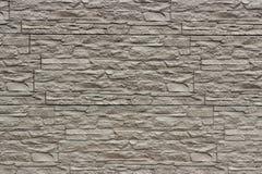 Διακοσμητικός μπεζ τοίχος της τεχνητής σχισμένης πέτρας ως υπόβαθρο ο Στοκ εικόνες με δικαίωμα ελεύθερης χρήσης