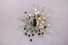 Διακοσμητικός τοίχος γύρω από τον καθρέφτη με μορφή του ήλιου, ένας χρυσός καθρέφτης βαρελοποιών, σύγχρονη μορφή στο Σκανδιναβικό Στοκ Εικόνα