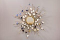 Διακοσμητικός τοίχος γύρω από τον καθρέφτη με μορφή του ήλιου, ένας χρυσός καθρέφτης βαρελοποιών, σύγχρονη μορφή στο Σκανδιναβικό Στοκ φωτογραφία με δικαίωμα ελεύθερης χρήσης