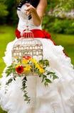 Διακοσμητικό άσπρο κλουβί για το πουλί με τα κόκκινα και κίτρινα λουλούδια και τα πράσινα φύλλα Στοκ Εικόνες