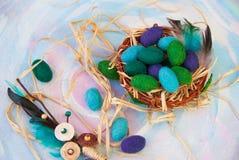 Διακοσμητικό αυγό Πάσχας με τα εσωτερικά και μάλλινα αυγά μωρών στο καλάθι Στοκ Εικόνα