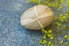 Διακοσμητικό αυγό Πάσχας Handcrafted που τυλίγεται στα μικρά κίτρινα λουλούδια ανοίξεων εγγράφου τεχνών στον γκρίζο πέτρινο τρύγο Στοκ Εικόνα