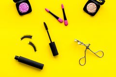 Διακοσμητικό καλλυντικό που τίθεται με το ρόλερ και mascara μαστιγίων στην κίτρινη τοπ άποψη υποβάθρου γραφείων γυναικών στοκ εικόνα