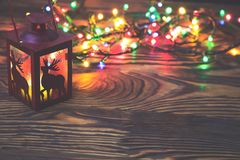 Διακοσμητικό κόκκινο φανάρι μετάλλων με μια διακοπή ελαφιών αναμμένη από ένα καμμένος κερί με το φως Χριστουγέννων και copyspace  Στοκ Εικόνες
