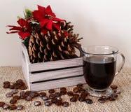 Διακοσμητικό ξύλινο κιβώτιο με τους κώνους πεύκων και poinsettia με την κούπα του μαύρου καφέ Στοκ εικόνα με δικαίωμα ελεύθερης χρήσης