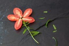 Διακοσμητικό λουλούδι από την ντομάτα στα μαύρα υπόβαθρα, υπόβαθρα τροφίμων Στοκ Φωτογραφία