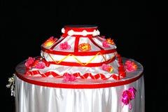 Διακοσμητικό πλαστό κέικ με τα λουλούδια και τις κόκκινες κορδέλλες Στοκ Εικόνες