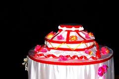 Διακοσμητικό πλαστό κέικ με τα λουλούδια και τις κόκκινες κορδέλλες στο μαύρο υπόβαθρο Στοκ Φωτογραφία