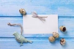 Διακοσμητικό πουλί, αυγά Πάσχας και κενή ετικέττα στην μπλε ξύλινη πλάτη Στοκ Εικόνα