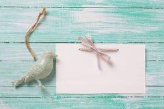 Διακοσμητικό πουλί και κενή ετικέττα στο τυρκουάζ ξύλινο υπόβαθρο Στοκ εικόνες με δικαίωμα ελεύθερης χρήσης
