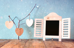 Διακοσμητικό πλαίσιο πινάκων κιμωλίας και ξύλινες κρεμώντας καρδιές πέρα από τον ξύλινο πίνακα έτοιμος για το κείμενο ή το πρότυπ Στοκ Φωτογραφία