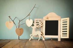 Διακοσμητικό πλαίσιο πινάκων κιμωλίας και ξύλινες κρεμώντας καρδιές πέρα από τον ξύλινο πίνακα έτοιμος για το κείμενο ή το πρότυπ Στοκ Εικόνες