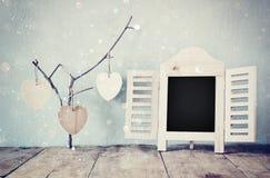 Διακοσμητικό πλαίσιο πινάκων κιμωλίας και ξύλινες κρεμώντας καρδιές πέρα από τον ξύλινο πίνακα έτοιμος για το κείμενο ή το πρότυπ Στοκ εικόνα με δικαίωμα ελεύθερης χρήσης