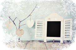 Διακοσμητικό πλαίσιο πινάκων κιμωλίας και ξύλινες κρεμώντας καρδιές πέρα από τον ξύλινο πίνακα έτοιμος για το κείμενο ή το πρότυπ Στοκ εικόνες με δικαίωμα ελεύθερης χρήσης