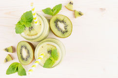 Διακοσμητικό πλαίσιο του πράσινου καταφερτζή φρούτων ακτινίδιων στα βάζα γυαλιού με το άχυρο, φύλλο μεντών, χαριτωμένο ώριμο μούρ Στοκ Φωτογραφίες
