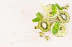 Διακοσμητικό πλαίσιο του πράσινου καταφερτζή φρούτων ακτινίδιων στα βάζα γυαλιού με το άχυρο, φύλλο μεντών, χαριτωμένο ώριμο μούρ Στοκ φωτογραφία με δικαίωμα ελεύθερης χρήσης