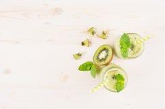 Διακοσμητικό πλαίσιο του πράσινου καταφερτζή φρούτων ακτινίδιων στα βάζα γυαλιού με το άχυρο, φύλλο μεντών, χαριτωμένο ώριμο μούρ Στοκ εικόνα με δικαίωμα ελεύθερης χρήσης