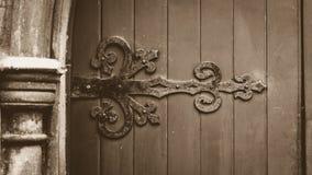 Διακοσμητικό σιδηρουργείο στην ξύλινη πόρτα στον τόνο σεπιών στοκ φωτογραφία με δικαίωμα ελεύθερης χρήσης
