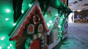 Διακοσμητικό σπίτι μελοψωμάτων σε μια εορταστική χειμερινή οδό φιλμ μικρού μήκους