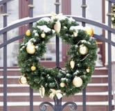 Διακοσμητικό στεφάνι Χριστουγέννων με τους πράσινους κλαδίσκους δέντρων έλατου και τα χρυσά παιχνίδια Στοκ Εικόνες