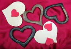 Διακοσμητικό υπόβαθρο ημέρας βαλεντίνων ` s ξύλινες καρδιές σε ένα κόκκινο υπόβαθρο μεταξιού χαιρετισμός καλή χρονιά καρτών του 2 στοκ εικόνα