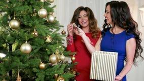 Διακοσμώντας ένα χριστουγεννιάτικο δέντρο, τα ευτυχή κορίτσια το βράδυ ντύνουν τη συζήτηση, γέλιο κατά τη διάρκεια να προετοιμαστ φιλμ μικρού μήκους