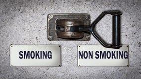 Διακόπτης τοίχων που καπνίζει εναντίον του μη καπνίσματος στοκ φωτογραφίες