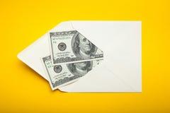 Διακόσια δολάρια σε έναν φάκελο σε ένα κίτρινο υπόβαθρο, δωροδοκία στοκ εικόνες