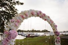 Διακόσμηση γαμήλιας οργάνωσης κατά τη διάρκεια της υποδοχής - τρυφερό ρόδινο και άσπρο χρώμα - υπαίθρια όμορφη αψίδα στοκ εικόνα