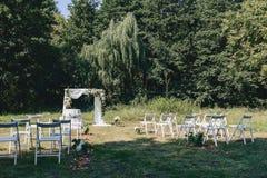 Διακόσμηση γαμήλιας τελετής, καρέκλες, αψίδες, λουλούδια και διάφορο ντεκόρ στοκ φωτογραφία