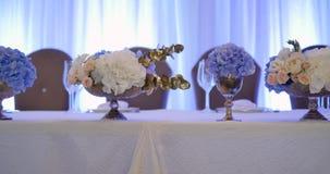 Διακόσμηση γαμήλιων πινάκων με τα λουλούδια, γαμήλιος πίνακας διακοσμήσεων λουλουδιών, γαμήλιος ανθοκόμος απόθεμα βίντεο